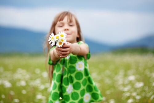 Niña con flores en las manos representando el representando el valor de la convivencia
