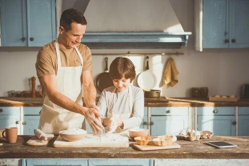 Padre enseñando a cocinar a su hijo para reducir la ansiedad por coronavirus
