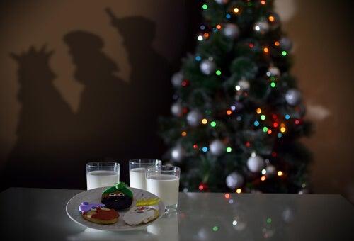 Vasos de leches con galletas al lado del árbol de Navidad