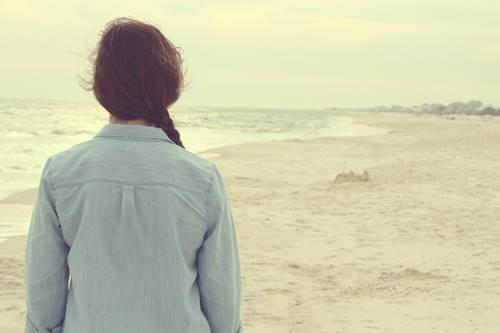 Mujer frente al mar pensando en e entrenar al cerebro para mantener la esperanza