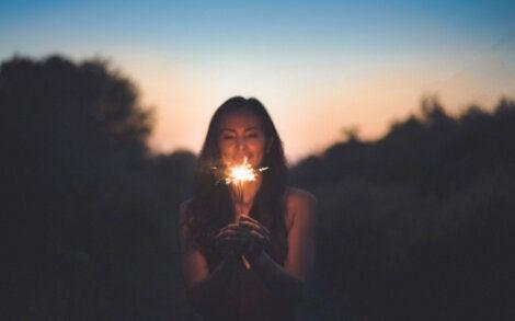 Mujer caminando con una luz entre sus manos