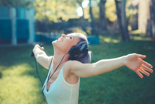 Mujer escuchando música con los brazos abiertos