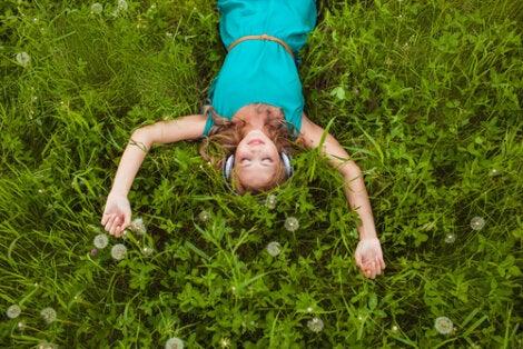 Mujer escuchando música tumbada en el suelo