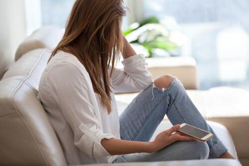 Mujer preocupada en el sofá pensando en la ansiedad por coronavirus