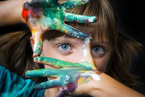 Niña con las manos llenas de pinturas