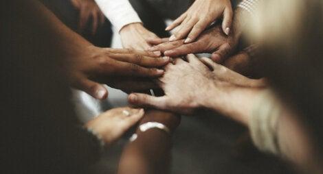 Manos unidas de muchas personas representando el representando el valor de la convivencia