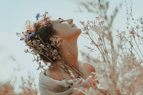 Mujer feliz entre flores pensando en que no debemos rendirnos