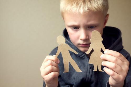 Niño sujetando dos figuras de cartón
