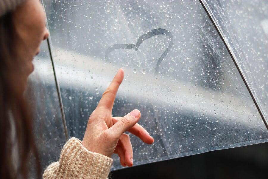 Chicas con un paraguas dibujando un corazón.