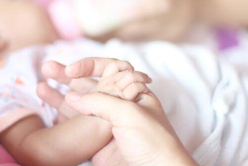Madre sujetando la mano del bebé