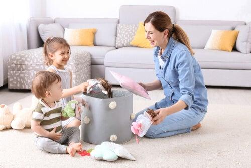 Madre recogiendo muñecos con sus hijos