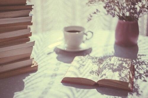 mesa con café y libros acumulados representando el Tsundoku