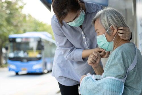 Mujer ayudando a una persona mayor a poner la mascarilla representando la responsabilidad individual durante el desconfinamiento