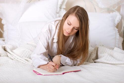 Mujer escribiendo en la cama