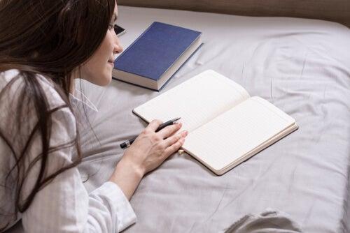 Mujer escribiendo en el diario de sueños