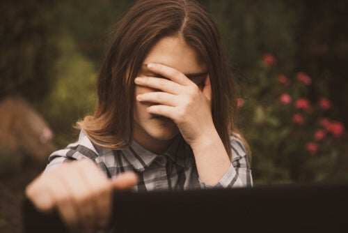 Mujer tapándose la cara por amenazas digitales