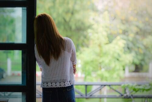 Mujer en la ventana pensando en la maternidad
