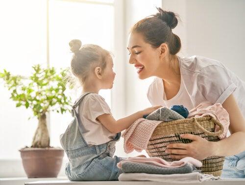 Niña recogiendo la ropa con su madre