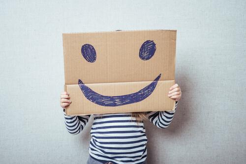 Niño con un cartón en el que hay dibujada una cara feliz