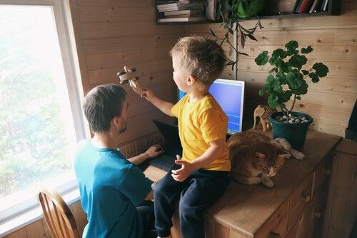 Niño jugando mientras su padre trabaja en casa