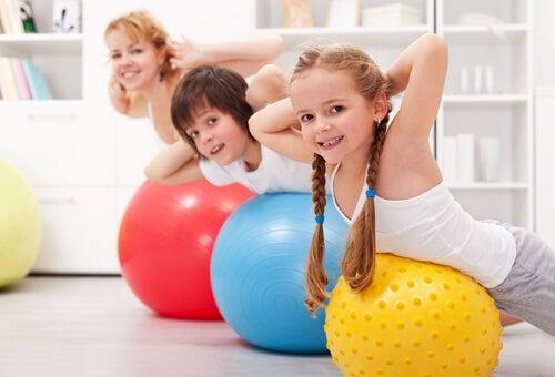 Niños haciendo deporte con su madre en casa