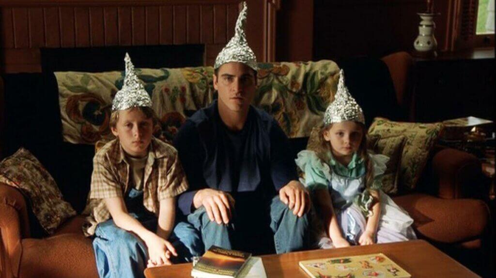 Adulto y niños con gorros de papel de aluminio
