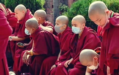 Monjes representando cómo manejan los budistas la crisis del coronavirus