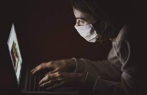 Chica con mascarilla ante ordenador representando el amor en tiempos de pandemia