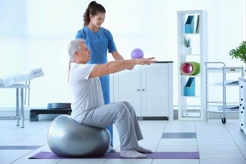Fisioterapeuta con un hombre mayor