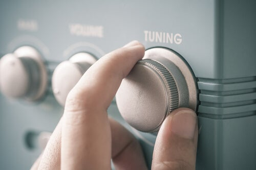 Mano encendiendo la radio