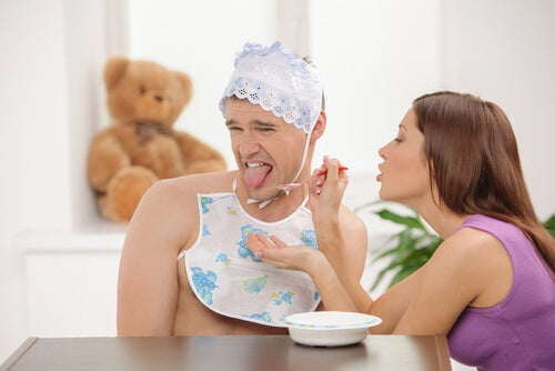 Hombre adulto vestido de bebé rechazando la comida