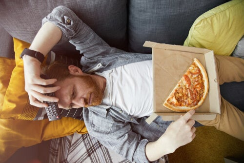 Hombre comiendo pizza aburrido