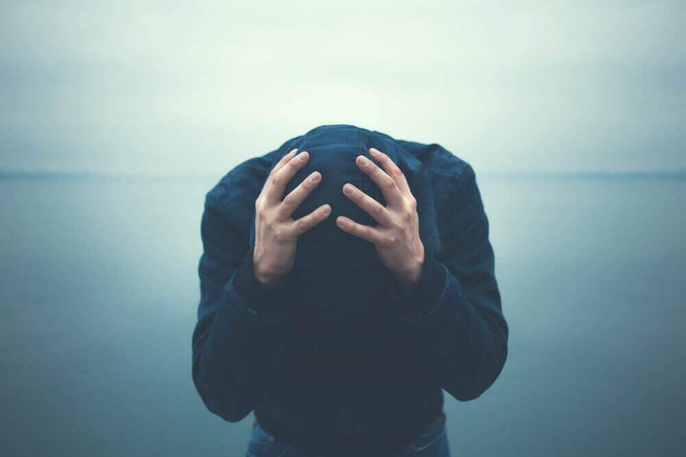 Chico llevándose manos a la cabeza para representar los distintos tipos de trastorno bipolar