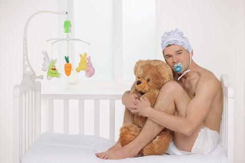 Hombre vestido de bebé abrazando a un oso