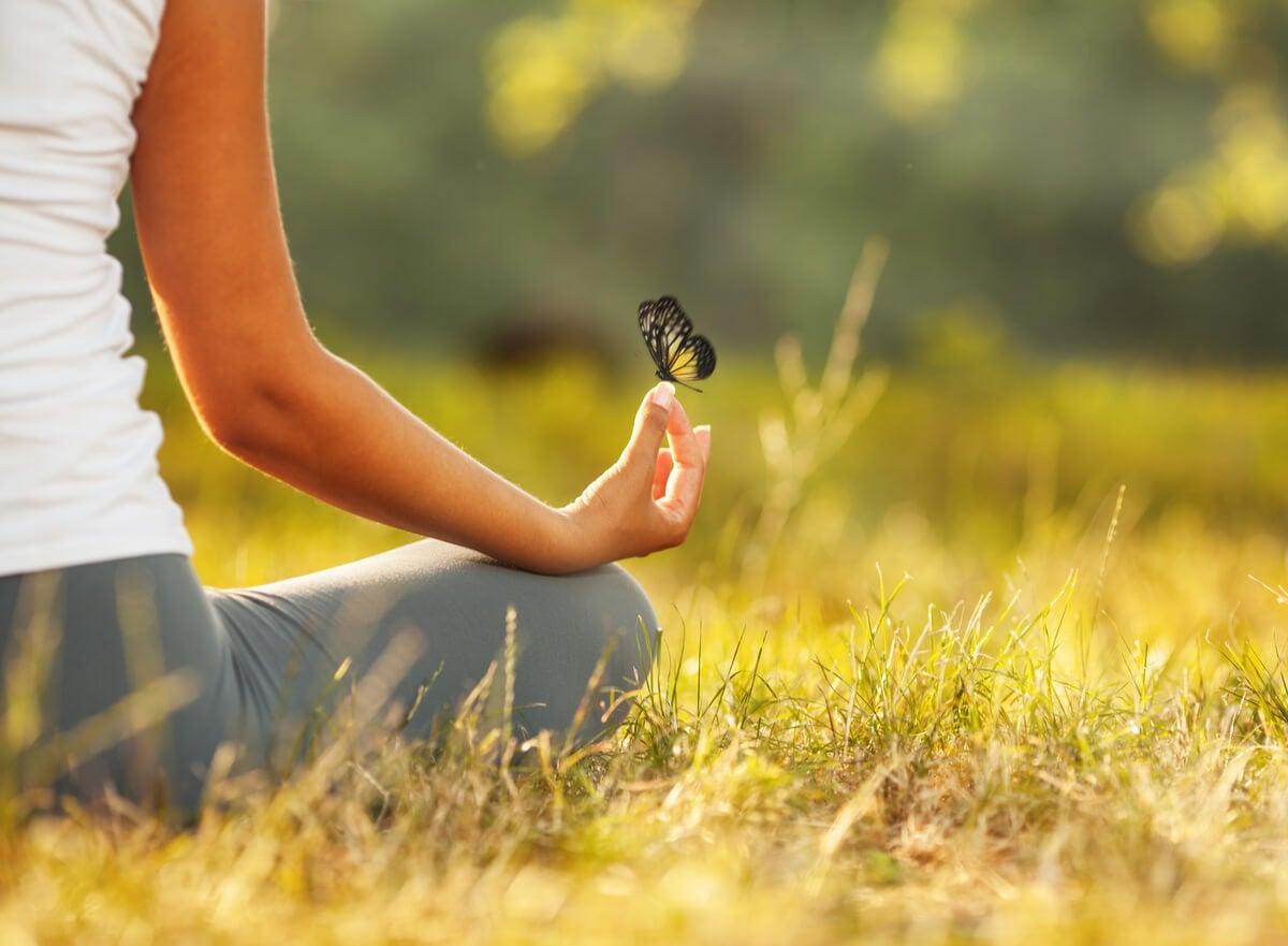 Mujer meditando con una mariposa en su mano