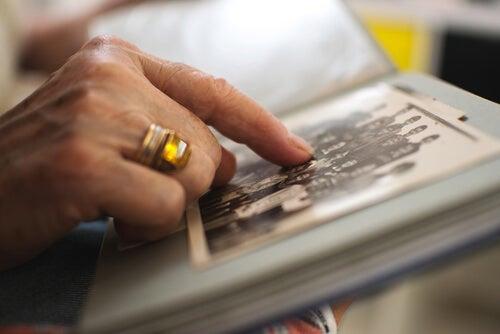 Mujer viendo un album de fotos como rito de despedida