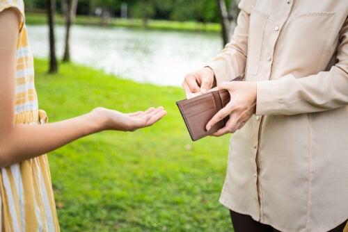 Padre dando dinero a su hija adolescente