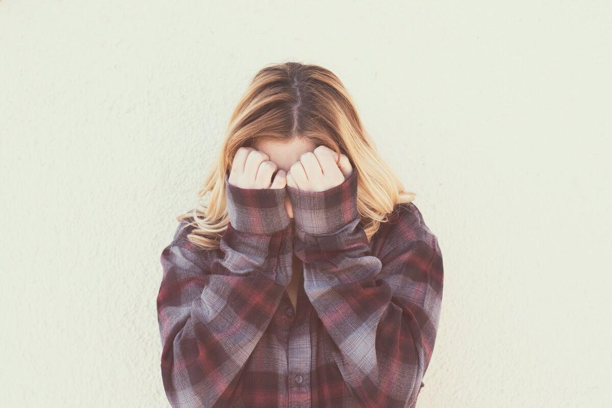 Adolescente tapándose la cara por vergüenza