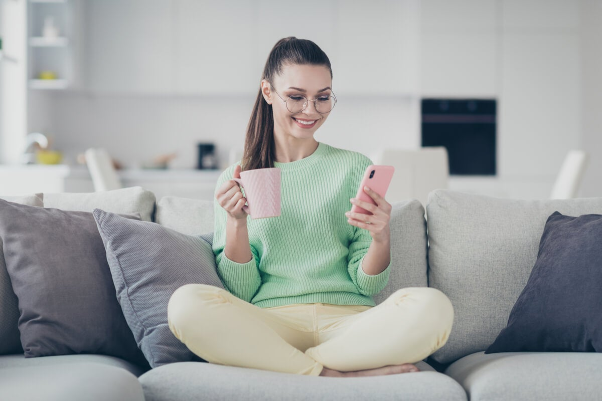 Chica con el móvil en el sofá
