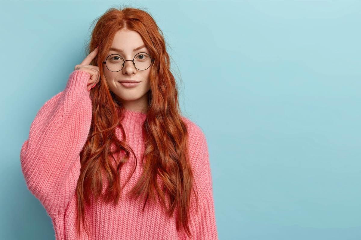 Chica pelirroja con gafas pensando en ¿por qué a veces hablamos solos?