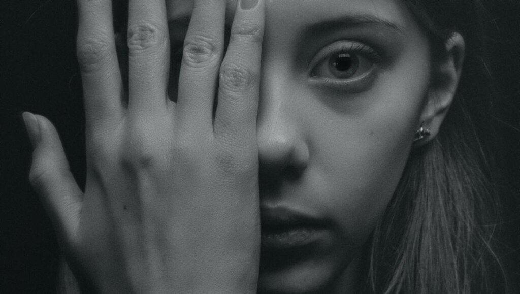 Mujer tapándose la cara con una mano