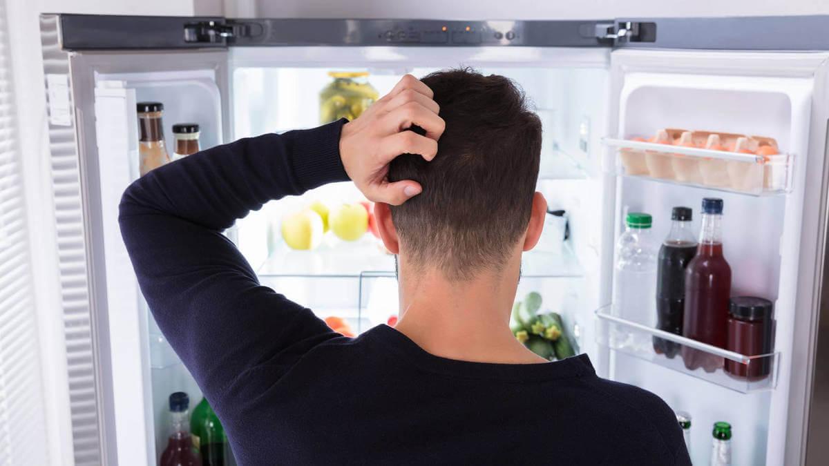 Hombre ante nevera abierta que sufre ansiedad por comer