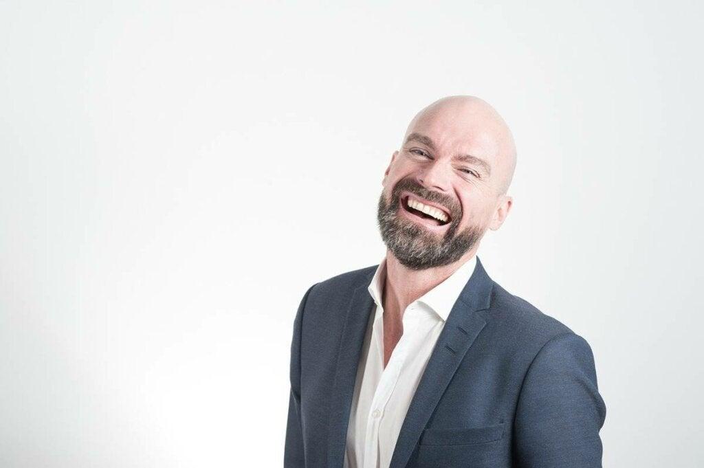 Hombre sonriendo feliz por desarrollar una personalidad más atractiva y carismática