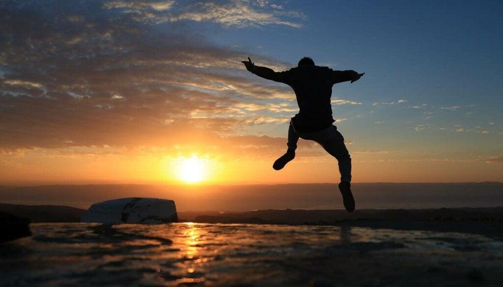 Hombre saltando feliz por tomar la iniciativa en una playa al amanecer