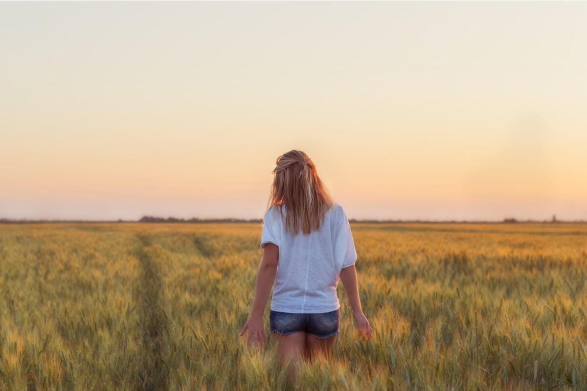 Mujer en un campo de trigo pensando que querer no es poder