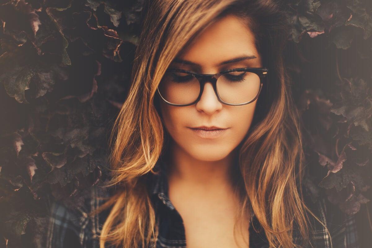 Mujer con gafas y los ojos cerrados pensando en bloquear los pensamientos negativos