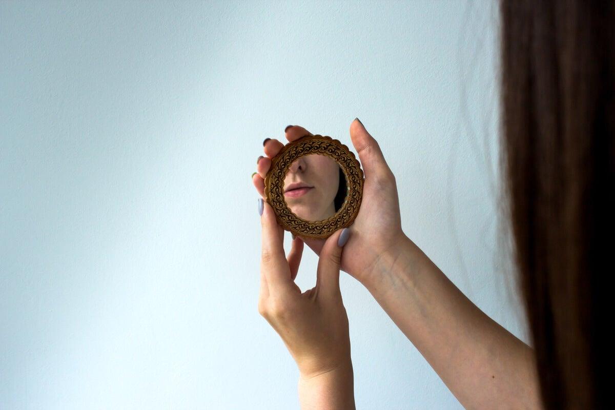 Mujer mirando su reflejo en el espejo