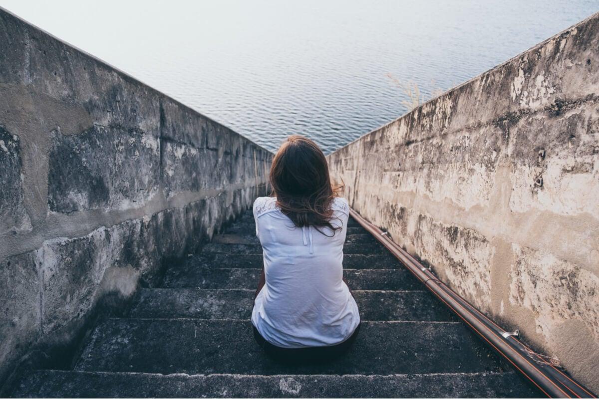 Mujer sentada en una escalera mirando el mar preguntándose si ¿Hay personas sin sentimientos?