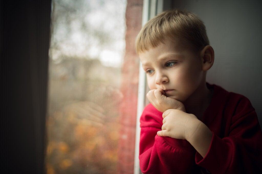 Niño preocupado en la ventana