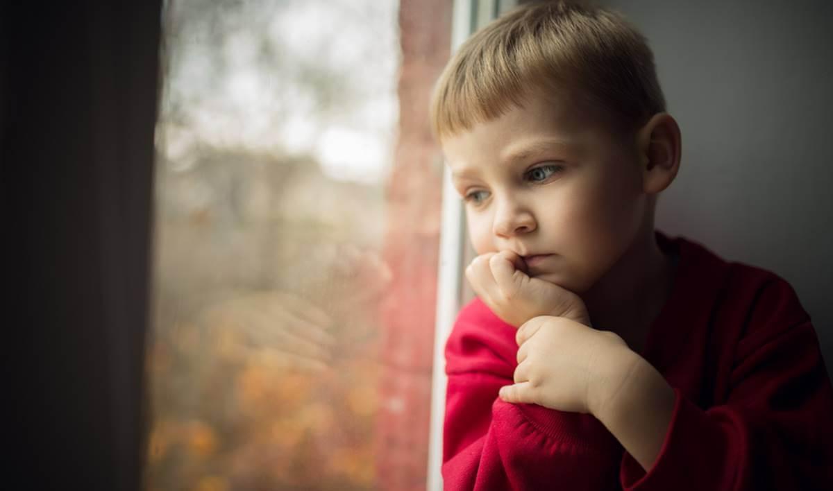 Niño triste representando el efecto de las madres que no quieren a sus hijos